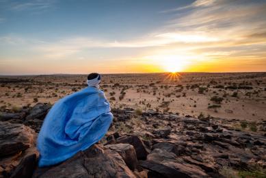 voyage photo dans le désert du sahara avec un chamelier en mauritanie au coucher du soleil